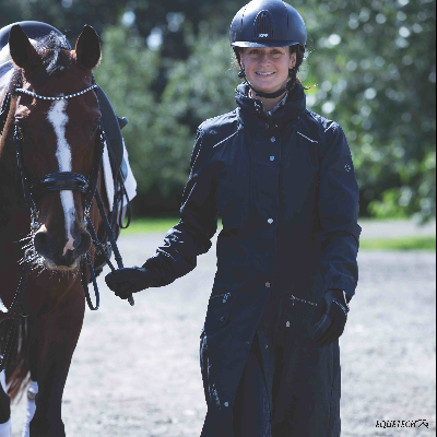 Rider wearing waterproof trench coat leading horse